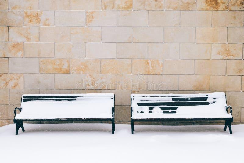 Snow-covered bank twee tegen een bakstenen muur in de winter royalty-vrije stock foto's