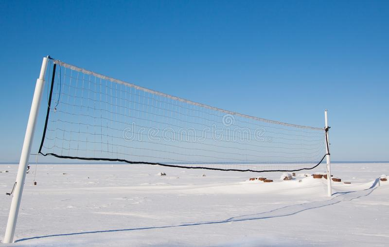 Snow covered beach volleyball court with net. Blue sky and deserted frozen bay background royalty free stock photography
