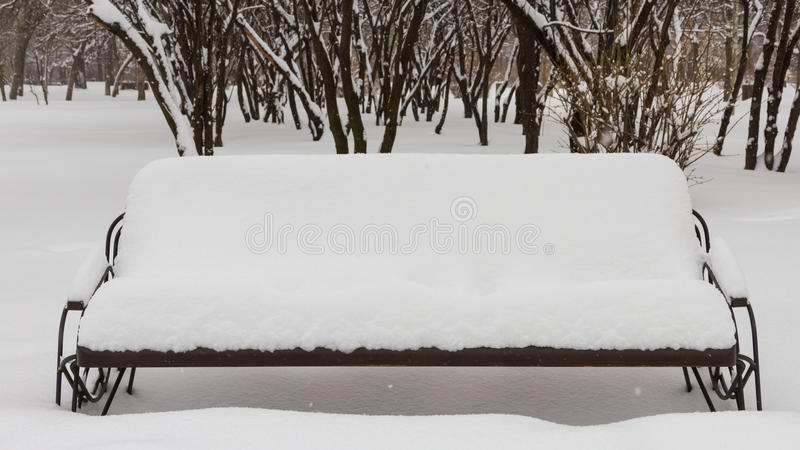 Snow covered bench. A snow cover bench in AIC Park stock image