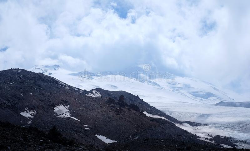 Snow-covered Berge und Wolken stockfotografie
