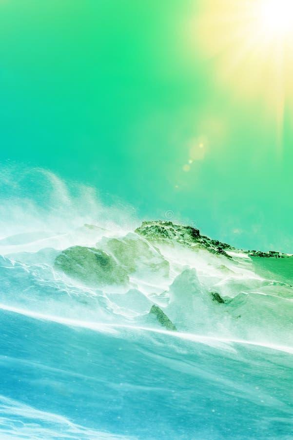 Snow-covered berghelling en heldere zon Wind en sneeuwstorm stock foto