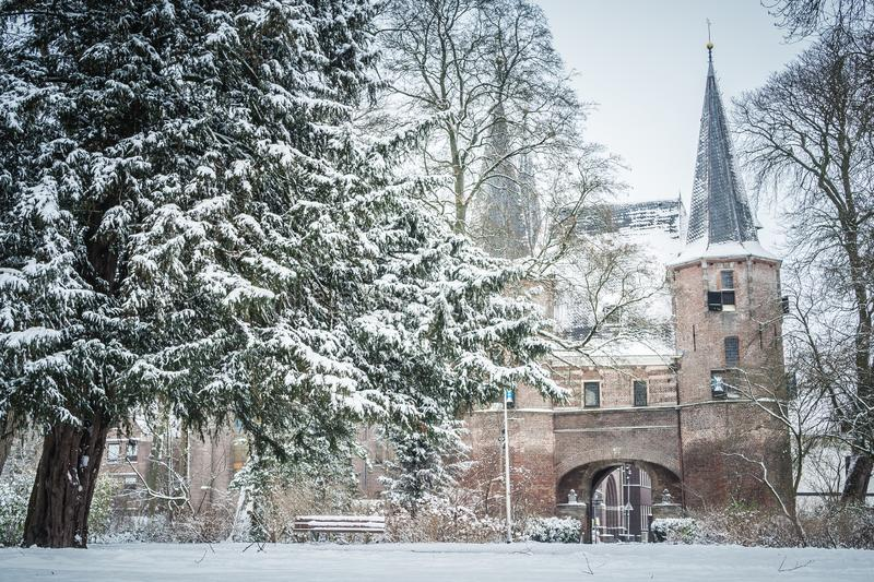 Snow covered Broederpoort and city park in Kampen, Netherlands on a winter morning. Kampen, Netherlands - January 23, 2019: snow covered Broederpoort and city royalty free stock image