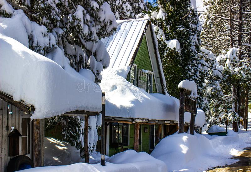 Snow covered building with peaked roof. Amidst snow laden trees stock photography