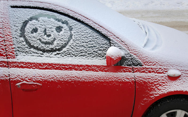 Snow covered car. Photo of a Snow covered car with a smiley royalty free stock photo