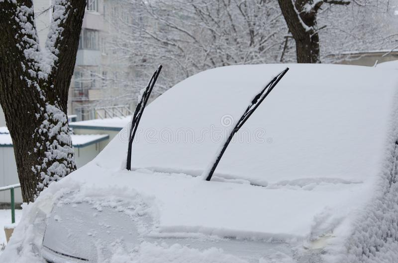 Snow-covered car. Parked cars in the snow cannot drive on the road. An emergency has been declared in the city.  stock photography