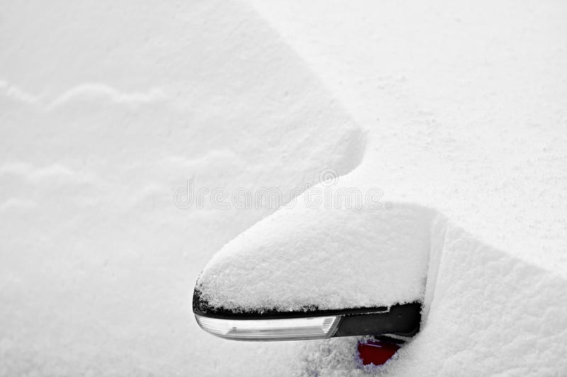 Snow covered car side mirror. Side mirror of a snow covered car during snowfall stock photography