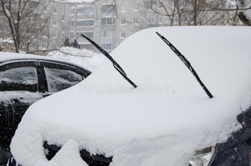 Snow-covered car with windscreen wiper during winter snowfall. Snow covered car with windscreen wiper during winter snowfall against bildings royalty free stock photos