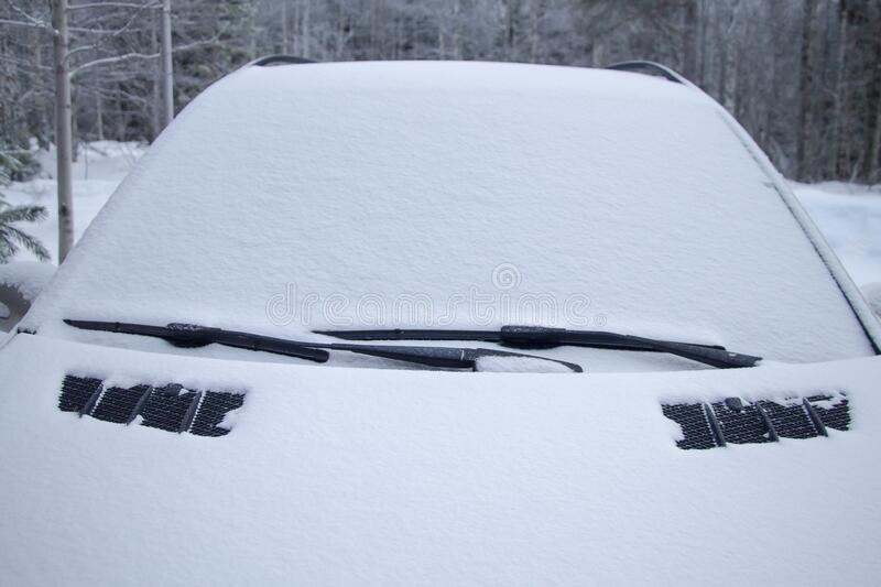 Snow covered car in the winter forest. The windshield is covered with snow.  stock photo