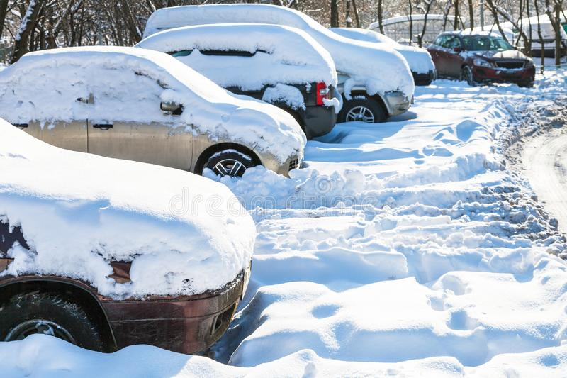 Snow-covered cars on car parking in winter. Snow-covered cars on car parking in Moscow city in sunny winter day stock photo