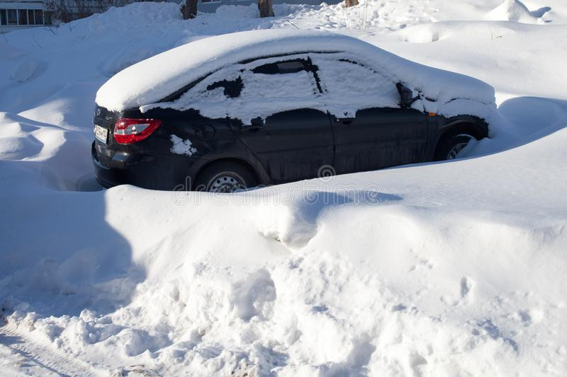 Snow-covered cars on the Parking lot, a snow storm in Russia. Snow removal utilities royalty free stock photos
