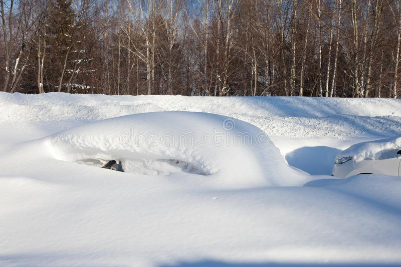 Snow-covered cars on the Parking lot, a snow storm in Russia. Snow removal utilities royalty free stock images