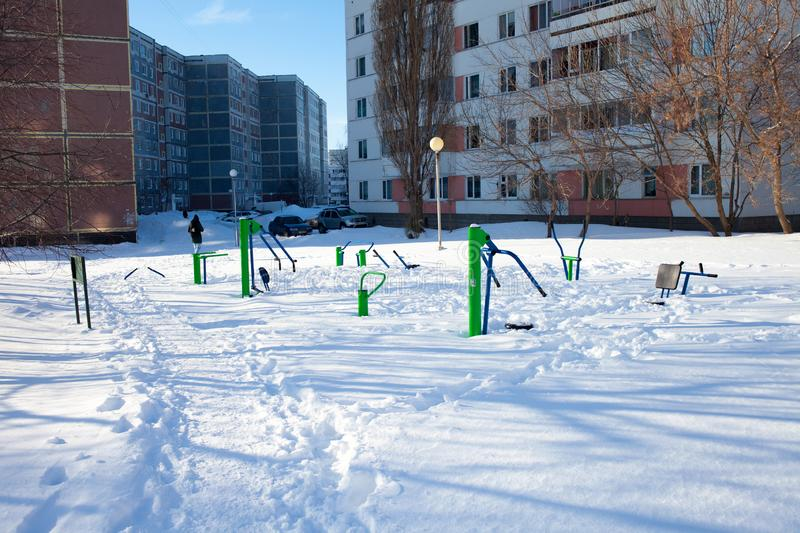 Snow-covered children`s and sports grounds in Russia. Poor cleaning of snow. Inaction of public services stock photo