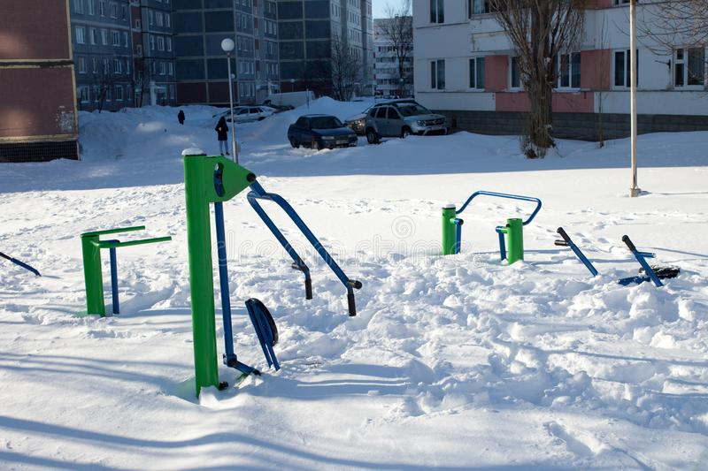 Snow-covered children`s and sports grounds in Russia. Poor cleaning of snow. Inaction of public services royalty free stock image