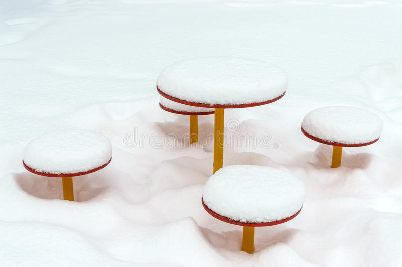 Snow-covered children`s table and benches. Snow caps on baby swing. Close-up. Winter landscape stock image