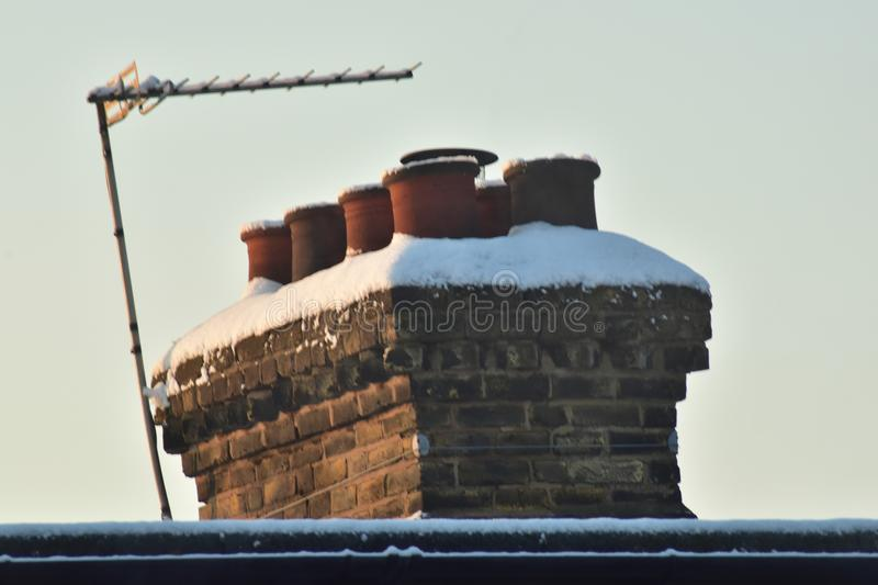 A snow covered chimney in the winter stock images