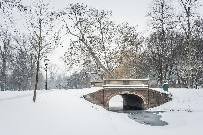 Snow covered city park in Kampen, Netherlands with pond and bridge on a winter morning. Kampen, Netherlands - January 23, 2019: snow covered city park with pond stock photo