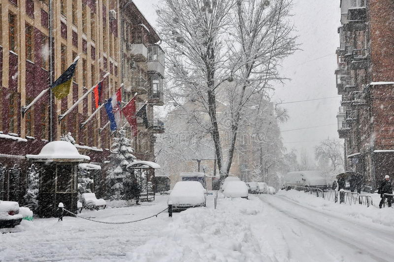 Snow-covered city street. Snowfall, snowdrift, city street with cars and buildings, flags royalty free stock photos