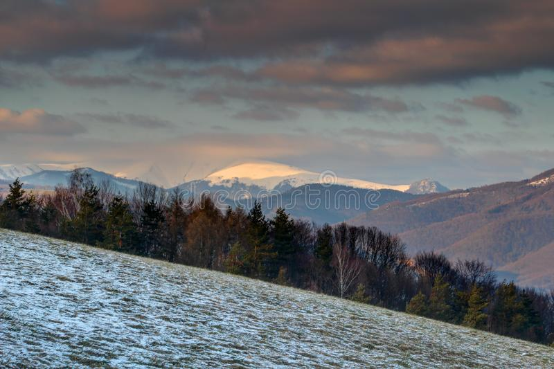 Snow-covered and cloud-capped peak Velka Fatra range Slovakia. Snow-covered and cloud-capped Krizna peak in Velka Fatra range of Carpathian mountains at sunset royalty free stock photos
