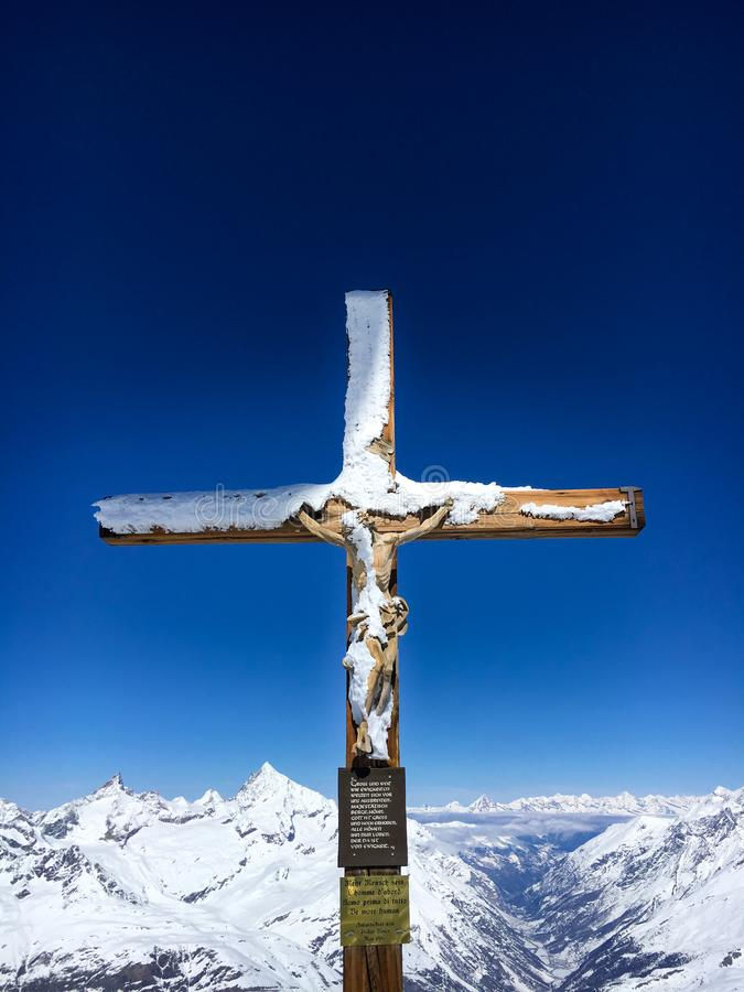 Cross with a wooden figure of Jesus Christ at peak of Klein Matterhorn mountain royalty free stock image
