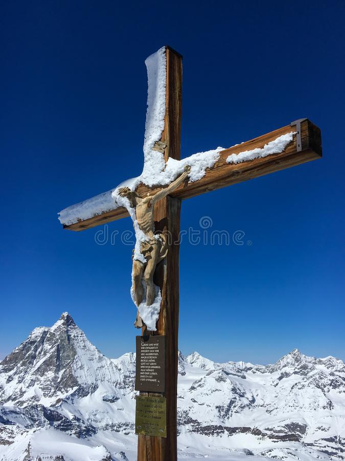 Cross with a wooden figure of Jesus Christ at peak of Klein Matterhorn mountain royalty free stock photo