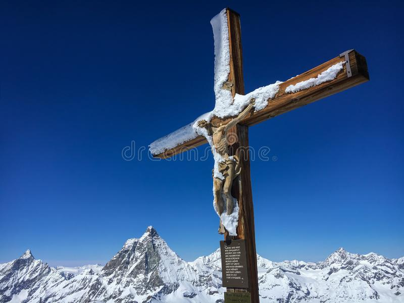 Cross with a wooden figure of Jesus Christ at peak of Klein Matterhorn mountain stock images