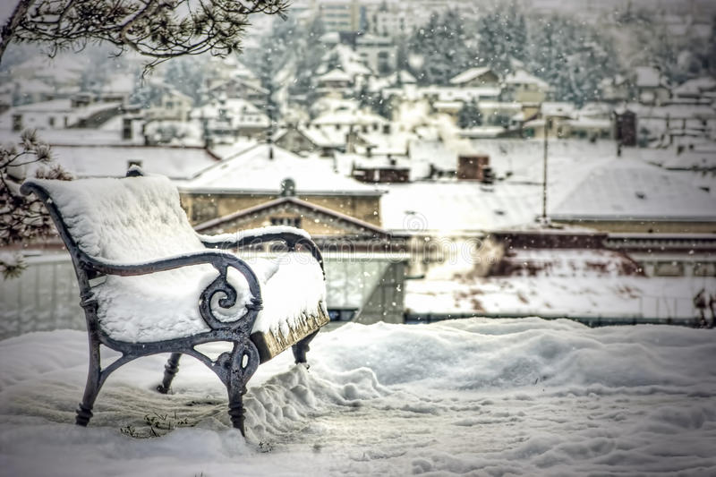 Snow covered empty bench. Bench in snowfall with city in background royalty free stock photo
