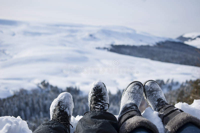 Snow-covered feet of two hikers on a winter landscape stock photography