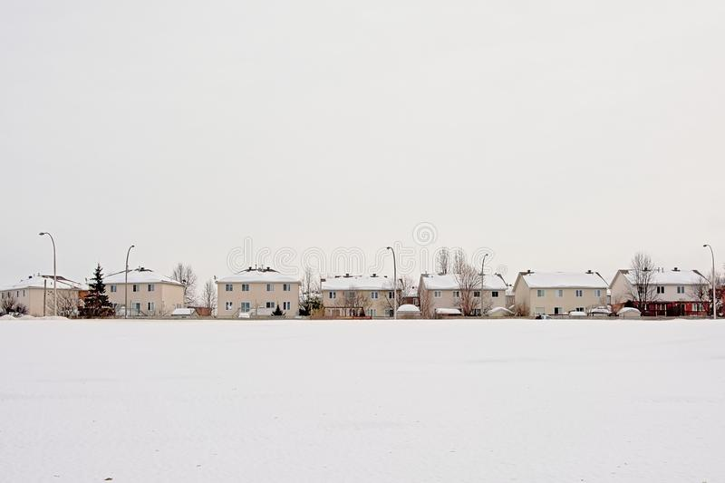 Snow covered field and row of suburban houses in Gatineau royalty free stock photography
