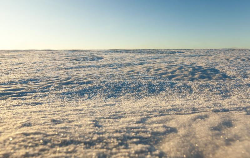 Snow-covered field. In winter, landscape with blue sky at sunset time royalty free stock photography