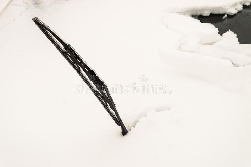 Snow covered front car window glass. Icy сar wiper sticking out of snow. royalty free stock photos