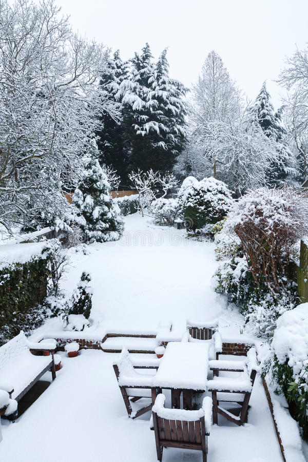 Snow covered garden and patio. Suburban winter garden and patio furniture covered with snow stock photo