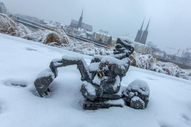 Snow covered gnome in a winter scenery, in the background a visible St. John the Baptist Cathedral - Wrocław, Poland royalty free stock photo