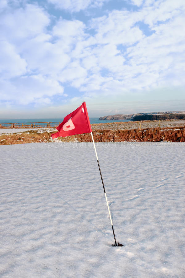 Snow covered golf course and cliffs with flag stock photo