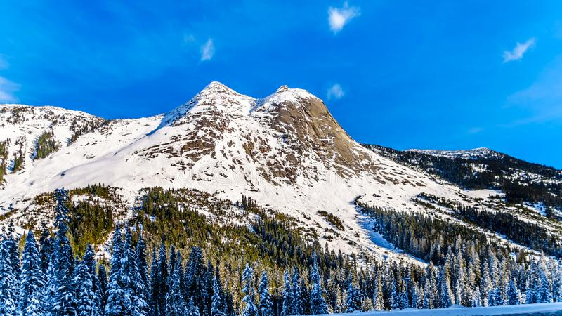 The snow covered granite rock face of Yak Peak in the Zopkios Ridge of the Cascade Mountain Range near the Coquihalla Summit. Seen from Highway 5, the stock photography