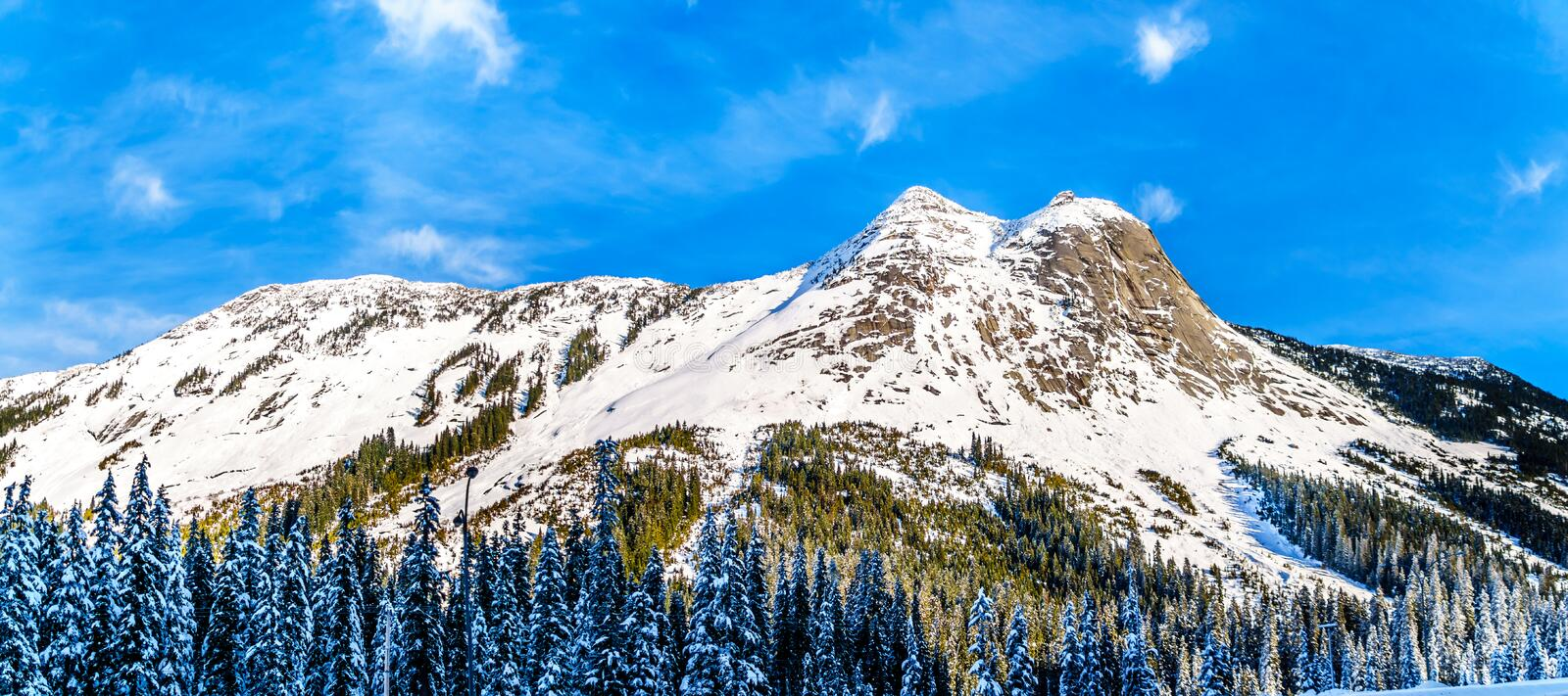 The snow covered granite rock face of Yak Peak in the Zopkios Ridge of the Cascade Mountain Range near the Coquihalla Summit. Seen from Highway 5, the stock image