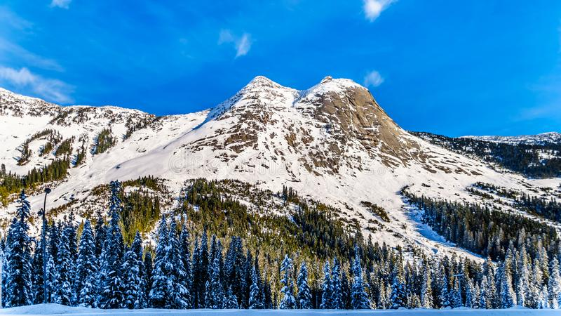 The snow covered granite rock face of Yak Peak in the Zopkios Ridge of the Cascade Mountain Range near the Coquihalla Summit. Seen from Highway 5, the stock photos