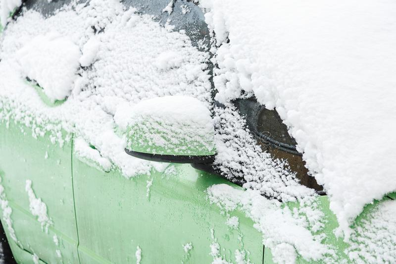 Snow covered green car on heavy snowy day. Driving safe. Concept stock photography