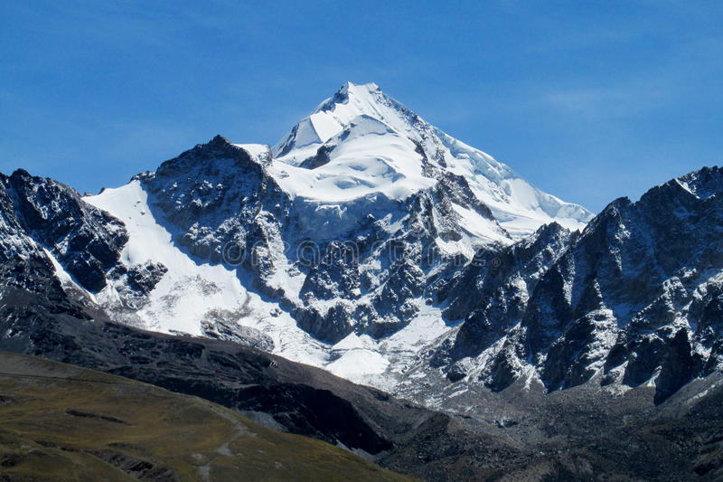 Snow covered high mountain view. From green valley. South America high Andes, Bolivia snow and ice glaciar mountain walls and summits. Beautiful trekking view stock photography