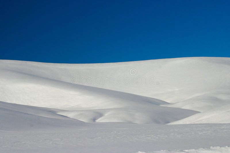 Snow Covered Hill. Undulating land covered in snow with clear blue sky royalty free stock image