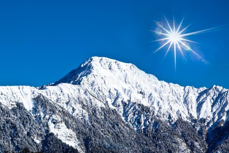 Snow-covered hoher Berg mit sonnigem Himmel lizenzfreies stockbild