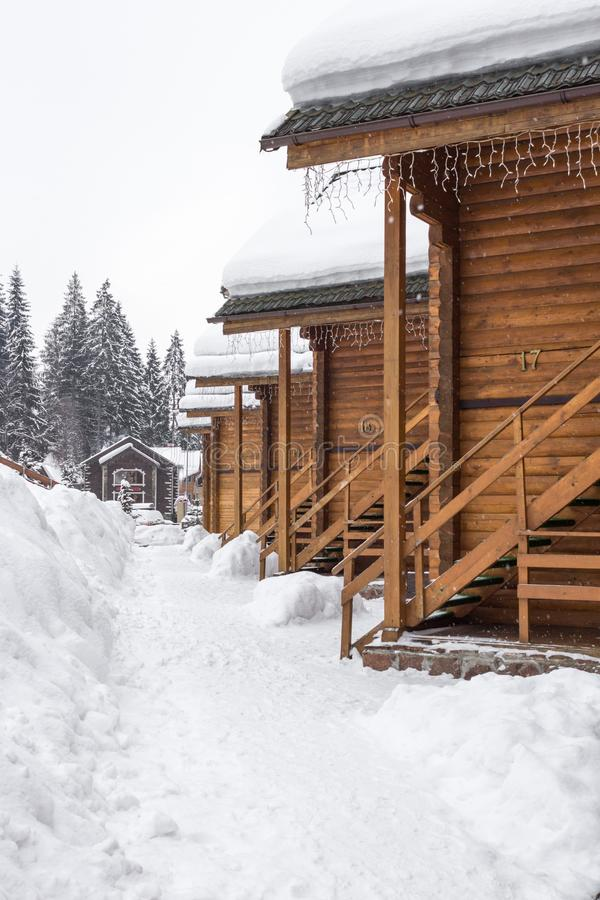 Snow-covered houses. Chalet in the ski resort. Wooden house in the resort Bukovel in Ukraine. Two-storey cottages of logs. Natural building materials. Winter stock images