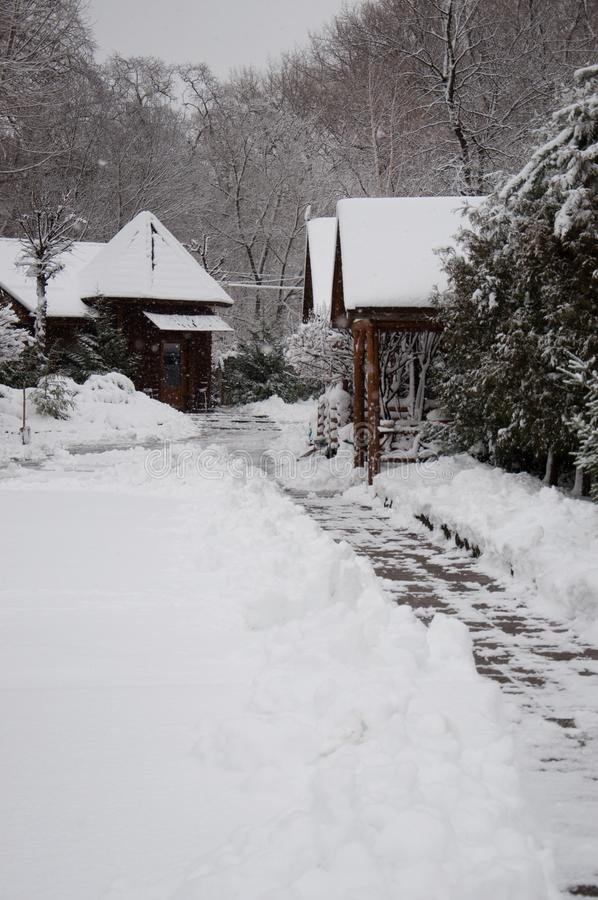 Snow-covered houses in a winter park, cleared a path of tiles and drifts. Outside, bad weather, snowstorm and snowdrifts royalty free stock images