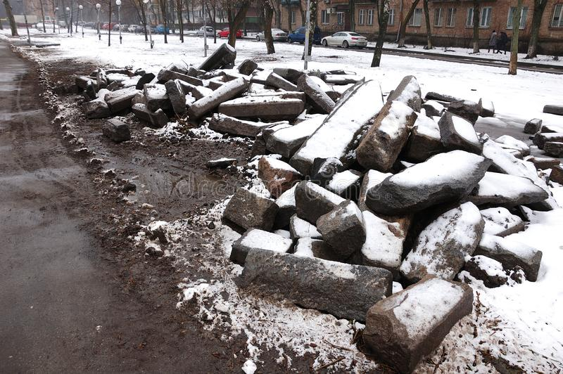 Snow-covered huge stones. Near the path in the park stock photos