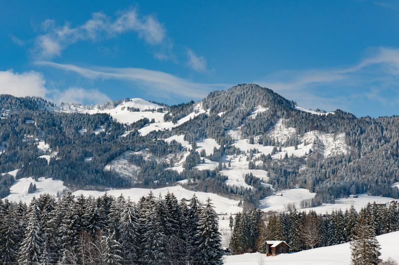 Snow covered landscape with fir forest and mountains, Bavaria, Germany royalty free stock photography