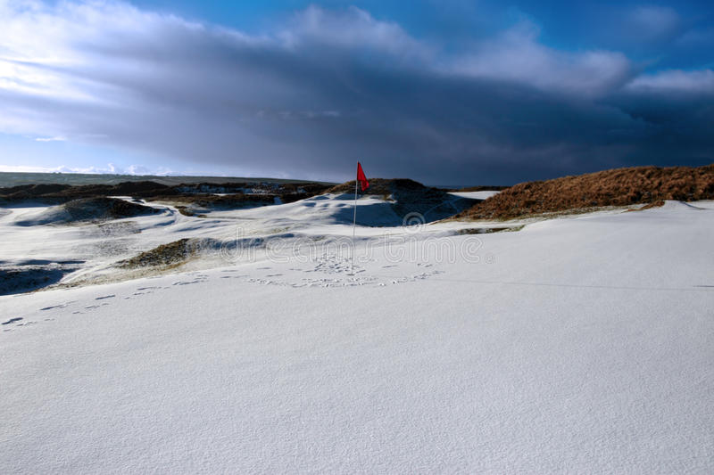 Snow covered links golf course red flag in storm. Red flag on a snow covered links golf course in ireland in stormy winter weather stock images