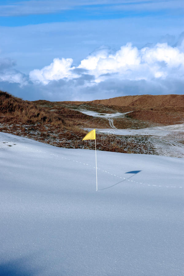 Snow covered links golf course with yellow flag. Yellow flag on a snow covered links golf course in ireland in winter royalty free stock image