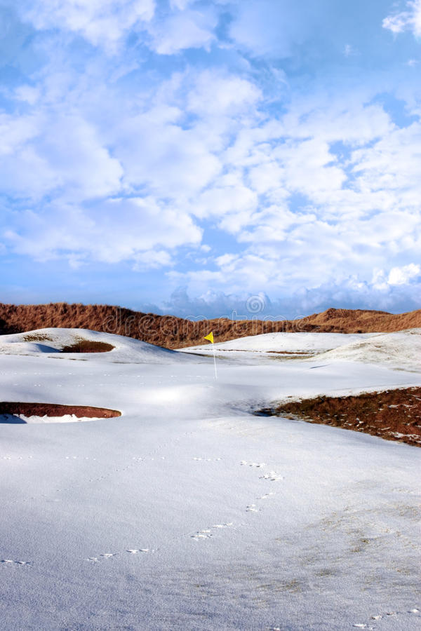 Snow covered links golf course with yellow flag. Yellow flag on a snow covered links golf course in ireland in winter royalty free stock photos