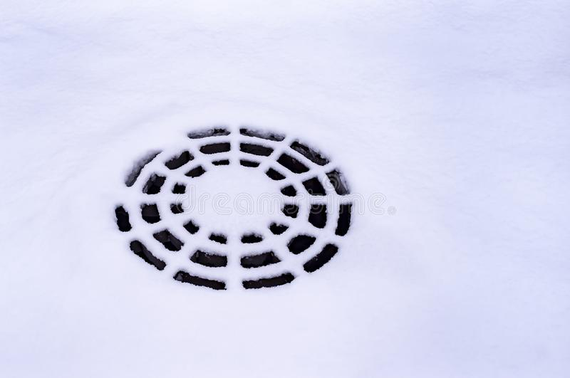 Snow-covered metal cover wastewater looks like a spider web royalty free stock photos