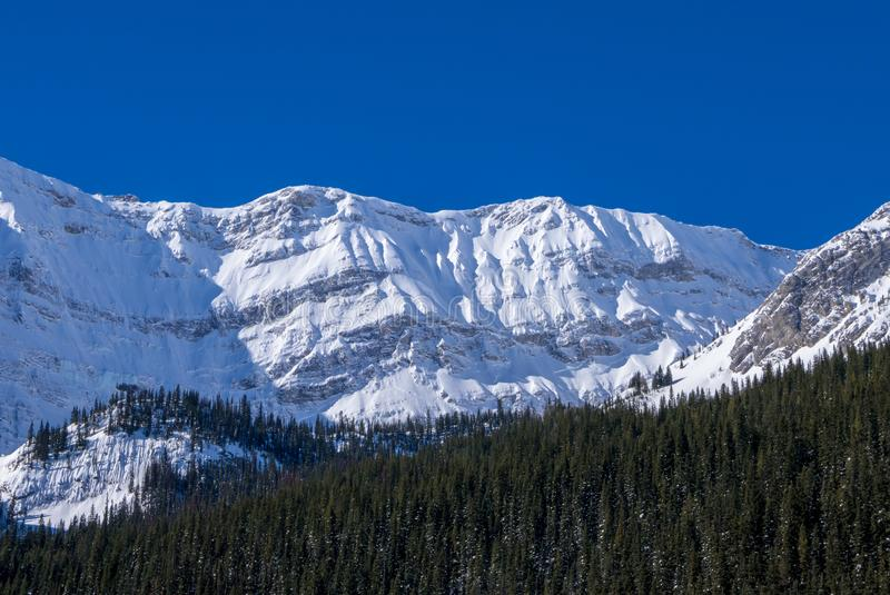 A snow covered mountain on a clear blue winter day in the Mountains at Black Prince Cirque in Kananaskis, Alberta stock photo
