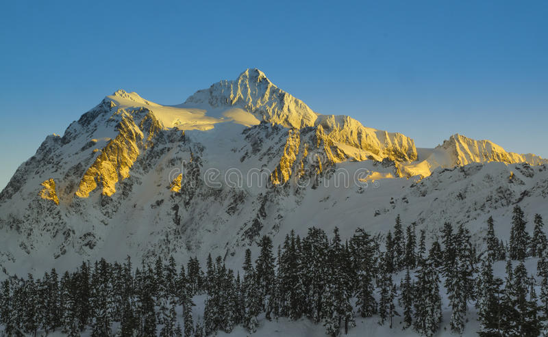 Snow covered mountain of Mt. Shuksan bathed in golden light. Snowcapped rugged mountain peak of Mount Shuksan towers in the North Cascades in Washington state stock photos